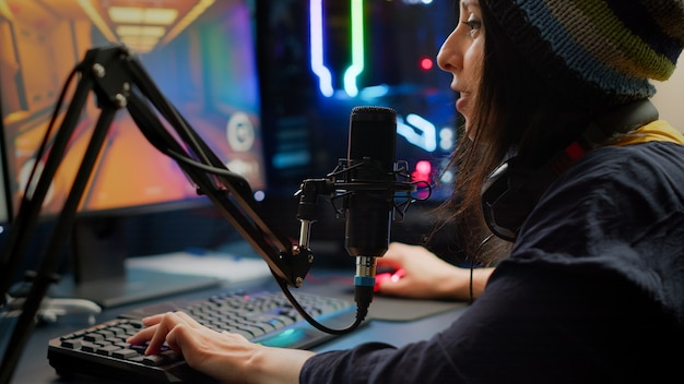Nahaufnahme eines streamers, der ein ego-shooter-videospiel mit rgb-tastatur und -maus spielt. spieler, die während eines esport-turniers spät in der nacht im gaming-studio über streaming-chat mit anderen spielern sprechen