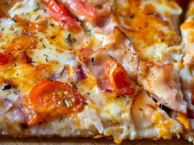 Nahaufnahme eines stücks saftiger pizza mit speckscheiben. ansicht von oben, flach. italienisches gericht