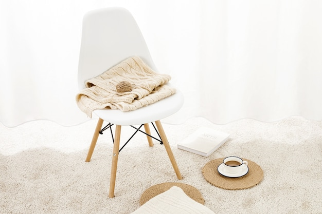 Nahaufnahme eines stuhls mit decken auf einem flauschigen teppich mit einer tasse kaffee und einem notizblock darauf on