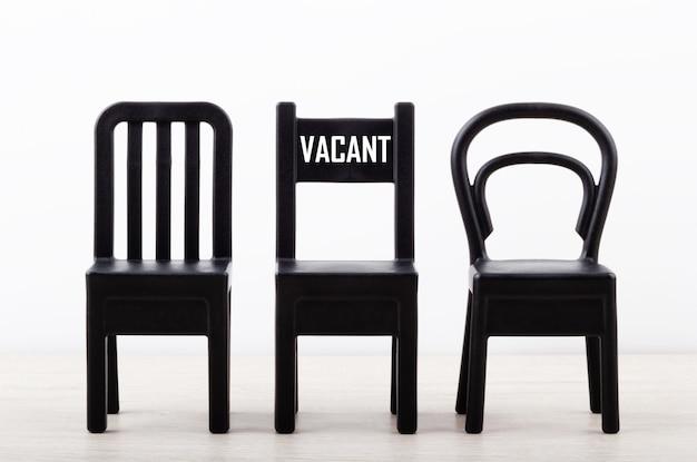Nahaufnahme eines stuhls mit text leerstand unter schwarzen stühlen in einer reihe