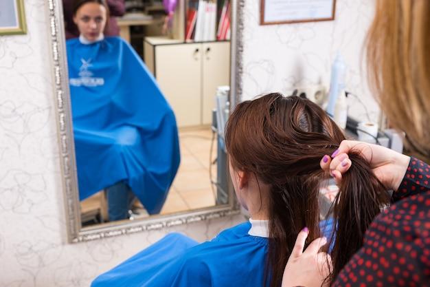Nahaufnahme eines stylisten, der feuchte haare von brünetten kunden im salon trennt, mit reflexion im großen spiegel im hintergrund