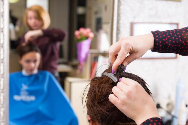 Nahaufnahme eines stylisten, der im salon einen clip in das nasse haar einer brünetten kundin mit unscharfer reflexion im hintergrundspiegel einsetzt