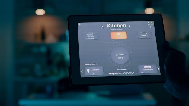 Nahaufnahme eines tablets mit aktiver smart-home-anwendung, die vom menschen gehalten wird