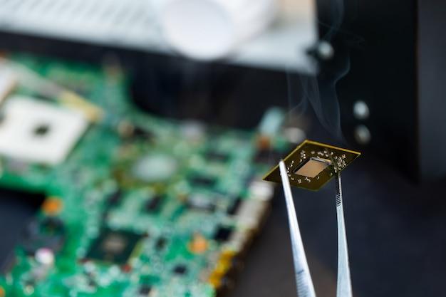 Nahaufnahme eines technikers, der einen computerchip mit einem lötkolben repariert, die teile erwärmt und sie von der platine trennt.