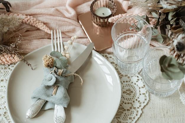 Nahaufnahme eines tellers mit besteck, verziert mit trockenen blumen in einem rustikalen stil.