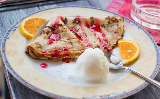 Nahaufnahme eines tellers mit krapfen pfannkuchen eiskugel roter belag orangenscheiben