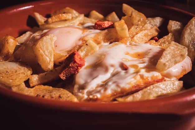 Nahaufnahme eines tellers mit rührei oder eiern mit chorizo und chips selektiver fokus