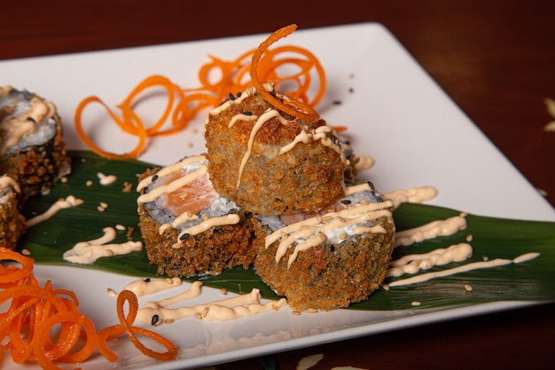 Nahaufnahme eines tellers tempura maki mit käse, zwiebeln und lachs. isoliertes bild