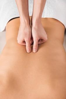 Nahaufnahme eines therapeuten, der der frau rückenmassage gibt