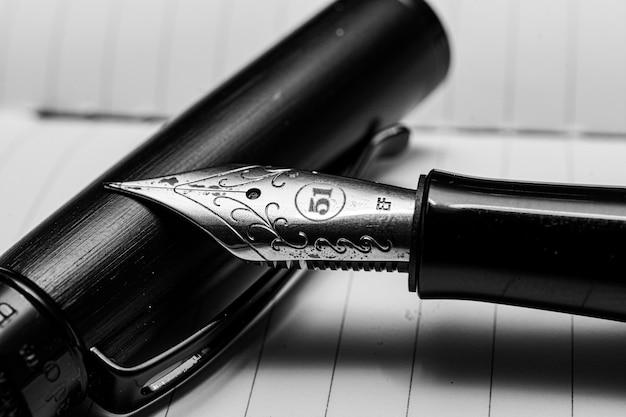 Nahaufnahme eines tintenschreibers auf dem weißen papier mit streifen