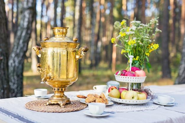 Nahaufnahme eines traditionellen russischen samowars mit tassen auf einem tisch mit snacks