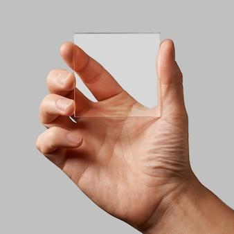 Nahaufnahme eines transparenten glases in den händen eines mannes auf einem grauen hintergrund kopieren raum für text