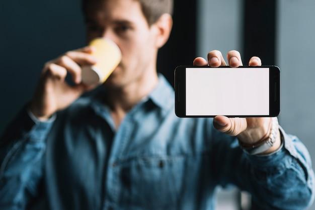 Nahaufnahme eines trinkenden kaffees des mannes, der mobiltelefon zeigt
