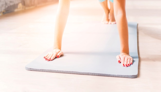 Nahaufnahme eines übenden yoga der frau auf übungsmatte