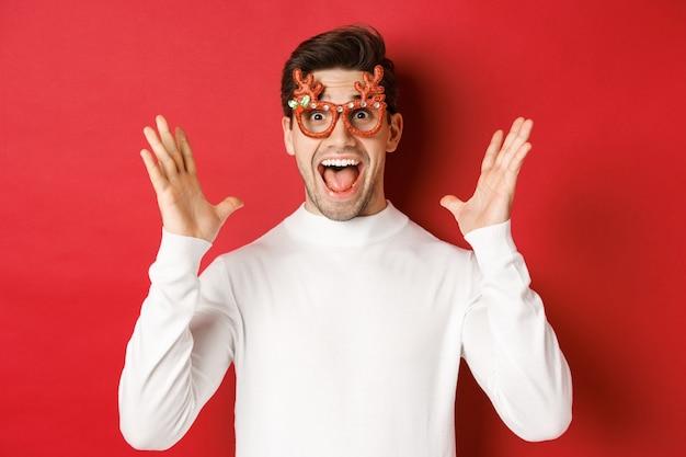 Nahaufnahme eines überraschten gutaussehenden kerls in weißem pullover und partybrille, hören sie ein tolles weihnachtsangebot, freuen sich und stehen auf rotem hintergrund.