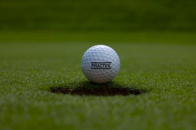Nahaufnahme eines übungstextes geschrieben auf einem golfball auf dem rasen unter dem sonnenlicht