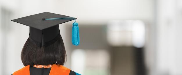 Nahaufnahme eines universitätsabsolventen im abschlusskleid, der eine abschlusszertifizierung mit mörtelboard hält, um den erfolg am college-starttag zu zeigen und zu feiern. bildung stockfoto