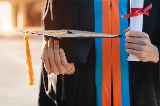Nahaufnahme eines universitätsabsolventen mit abschlusszertifikat, um seinen erfolg am college-starttag mit sonnenlicht im hintergrund zu zeigen und zu feiern.