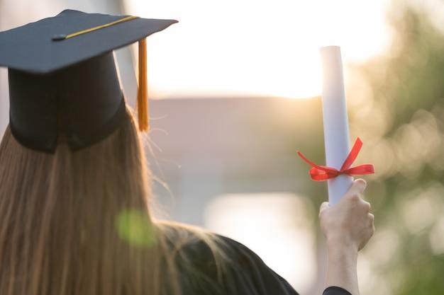 Nahaufnahme eines universitätsabsolventen mit einer abschlusszertifizierung, um den bildungserfolg am college-beginn zu zeigen und zu feiern. bildung stockfoto
