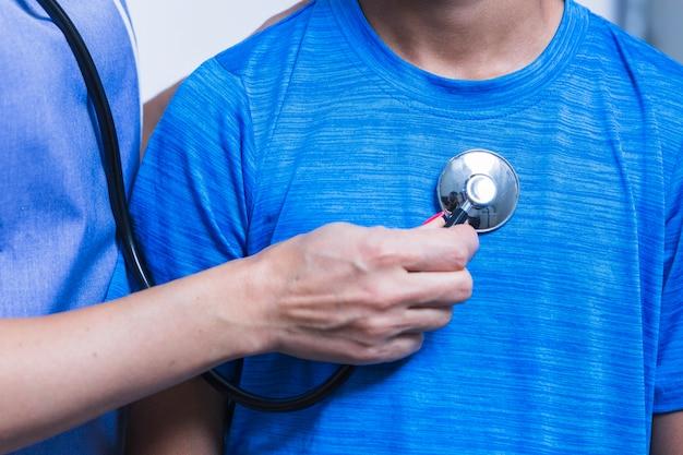Nahaufnahme eines untersuchenden patienten der zahnarzthand mit stethoskop