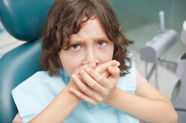 Nahaufnahme eines verängstigten kleinen jungen, der sich weigert, seinen mund für die zahnbehandlung zu öffnen?