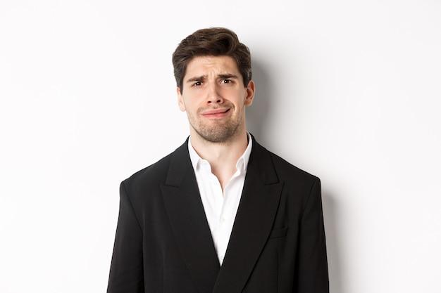 Nahaufnahme eines verwirrten gutaussehenden mannes im anzug, der eine grimasse verzieht und verwirrt aussieht, einen trendigen anzug trägt und vor weißem hintergrund steht.