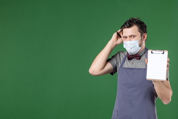 Nahaufnahme eines verwirrten männlichen kellners in uniform mit medizinischer maske und auftragsbuch auf grünem hintergrund