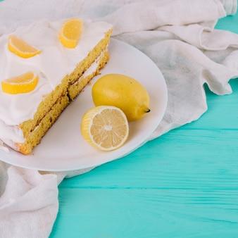 Nahaufnahme eines verzierten zitronenkuchens in der weißen platte mit zitronen auf holztisch
