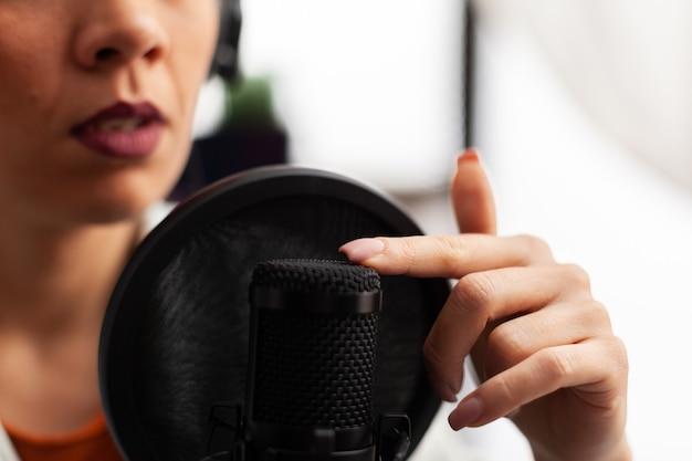 Nahaufnahme eines vloggers, der auf das mikrofon tippt, bevor ein youtube-video erstellt wird. influencerin, die professionelles equipment aufnimmt, sich selbst filmt und spaß daran hat, technologie zu nutzen, um mit der öffentlichkeit in kontakt zu treten.