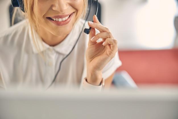 Nahaufnahme eines weiblichen callcenter-mitarbeiters, der das headset-mikrofon berührt und lächelt