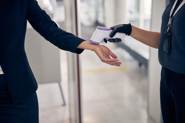 Nahaufnahme eines weiblichen flughafenwächters, der die temperatur der dame mit einem digitalen medizinischen thermometer misst