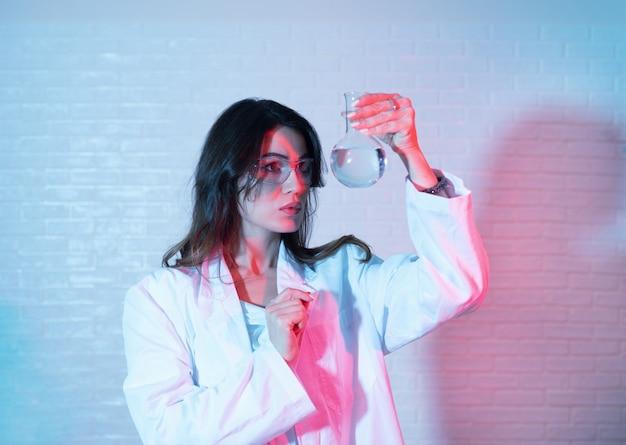 Nahaufnahme eines weiblichen forschers, der ein experiment in einem labor durchführt