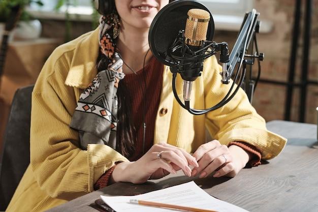 Nahaufnahme eines weiblichen radio-djs, der während der ausstrahlung im radio im mikrofon an ihrem arbeitsplatz sitzt
