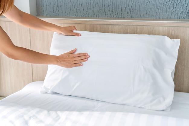 Nahaufnahme eines weiblichen zimmermädchens, das bett im hotelzimmer macht. speicherplatz kopieren