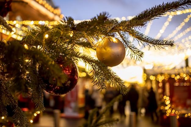Nahaufnahme eines weihnachtsbaumastes mit dekorativen kugeln, spielzeug und einer glänzenden girlande. weichzeichner, hintergrund in unschärfe.