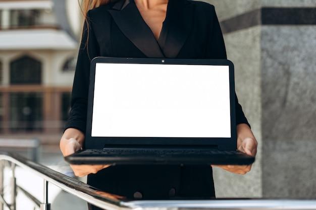 Nahaufnahme eines weißen bildschirms des leeren modells des laptops in den weiblichen händen - bild