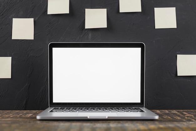 Nahaufnahme eines weißen laptops des leeren bildschirms auf holztisch