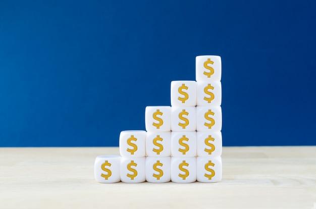 Nahaufnahme eines weißen würfels mit dollarzeichen auf ihnen gestapelt in einer form des wachsenden graphen. konzept des finanziellen wachstums.