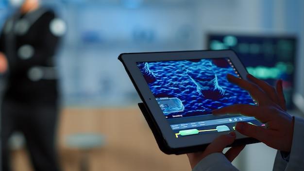 Nahaufnahme eines wissenschaftlers, der gesundheitsinformationen in tablet analysiert, während der fachsport die ausübung des sportlers überwacht, der seine körperliche ausdauer überwacht. untersuchung des medizinischen scans im notizblock im labor