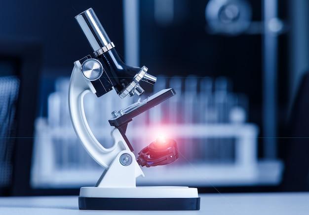 Nahaufnahme eines wissenschaftlichen mikroskopinstruments mit leuchtendem lichtfleck an linse und glasplattenprobe im laborarbeitstisch zur überwachung von coronavirus covid 19.