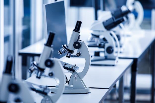 Nahaufnahme eines wissenschaftlichen mikroskops mit zwei augen-suchern in einer reihe von ein-augen-mikroskopen in verschwommenem vordergrund auf dem laborarbeitstisch zur überwachung von coronavirus-kovid-19-virusproben.