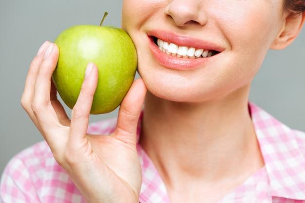 Nahaufnahme eines womans lächelns und eines grünen apfels gesundes zahnkonzept