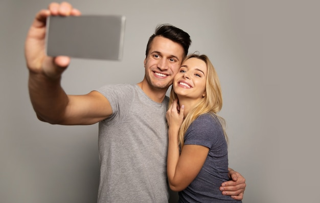Nahaufnahme eines wunderschönen mädchens und eines attraktiven mannes in lässigen outfits, die sich umarmen, während sie zusammen für ein selfie posieren.