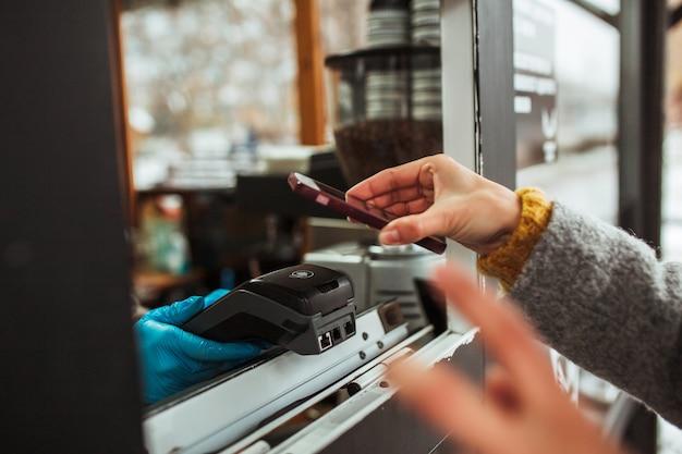 Nahaufnahme eines zahlungsterminals und eines mobiltelefons in den händen der frau, die für kaffee bezahlen.