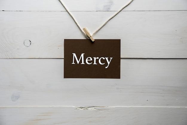 Nahaufnahme eines zeichens, das an einem seil mit barmherzigkeit angebracht ist, das darauf geschrieben wird