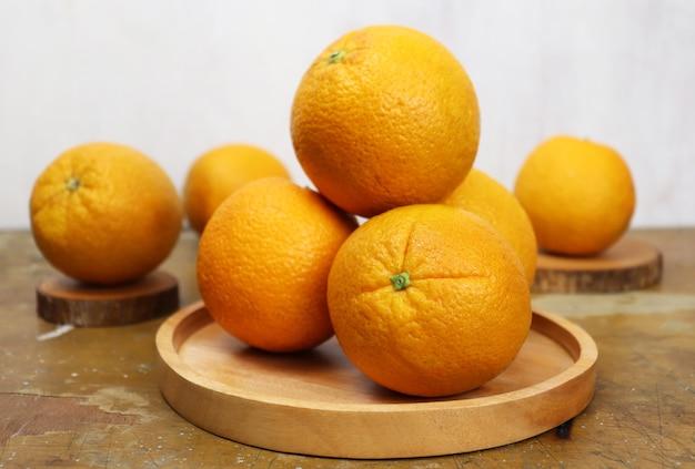 Nahaufnahme einiger frischer nabel-orangen mit holzplatte auf holztisch