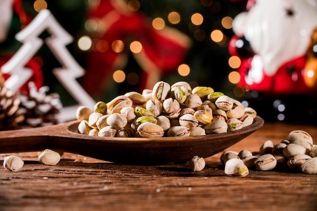 Nahaufnahme einiger gerösteter pistazien auf rustikalem altem holztisch