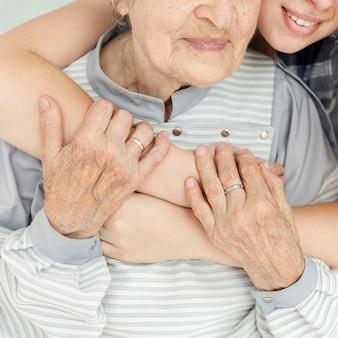Nahaufnahme enkelin, die großmutter umarmt