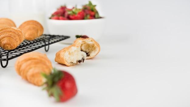 Nahaufnahme erdbeeren mit croissants auf dem tisch
