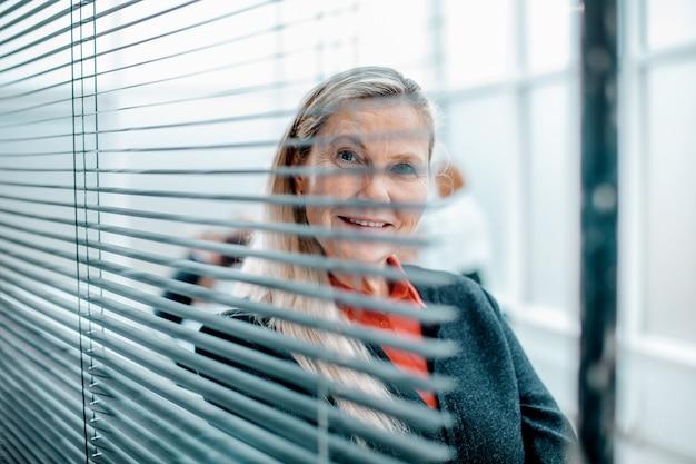 Nahaufnahme. erfolgreiche geschäftsfrau, die durch jalousien schaut.